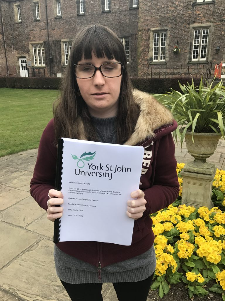 Holly holding her completed dissertation which has been printed and bound, it looks a bit like a book