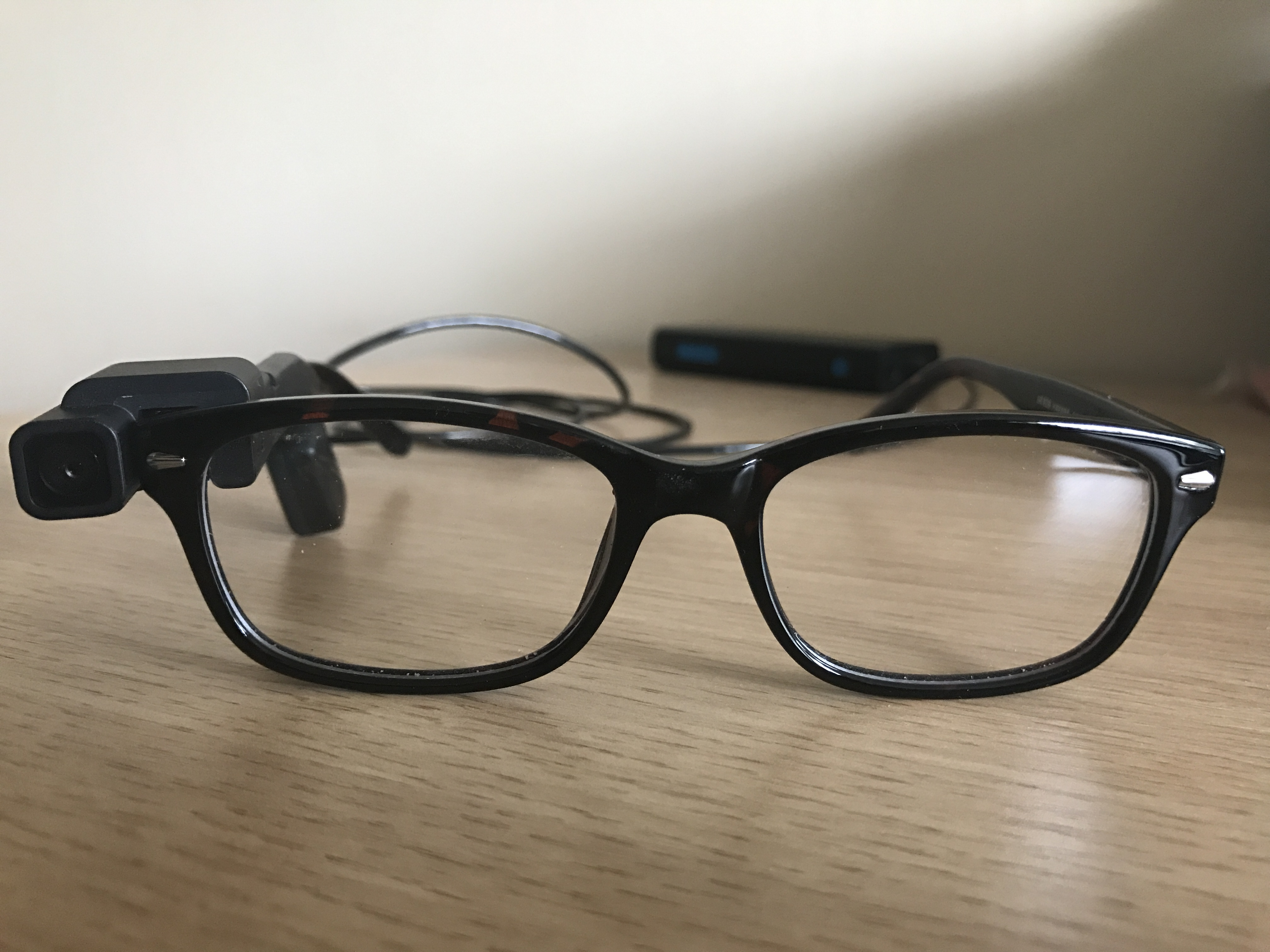 Photo shows an OrCam attached to a pair of glasses
