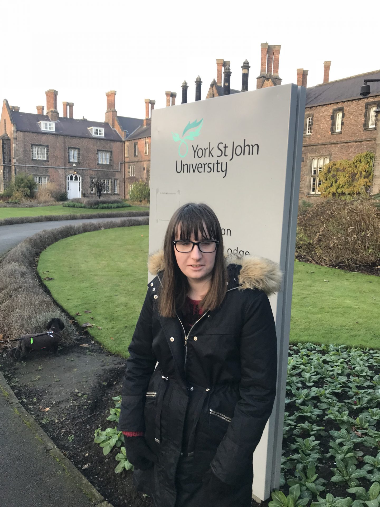Holly standing outside one of the buildings at York St John University, with the York St John University sign in the background