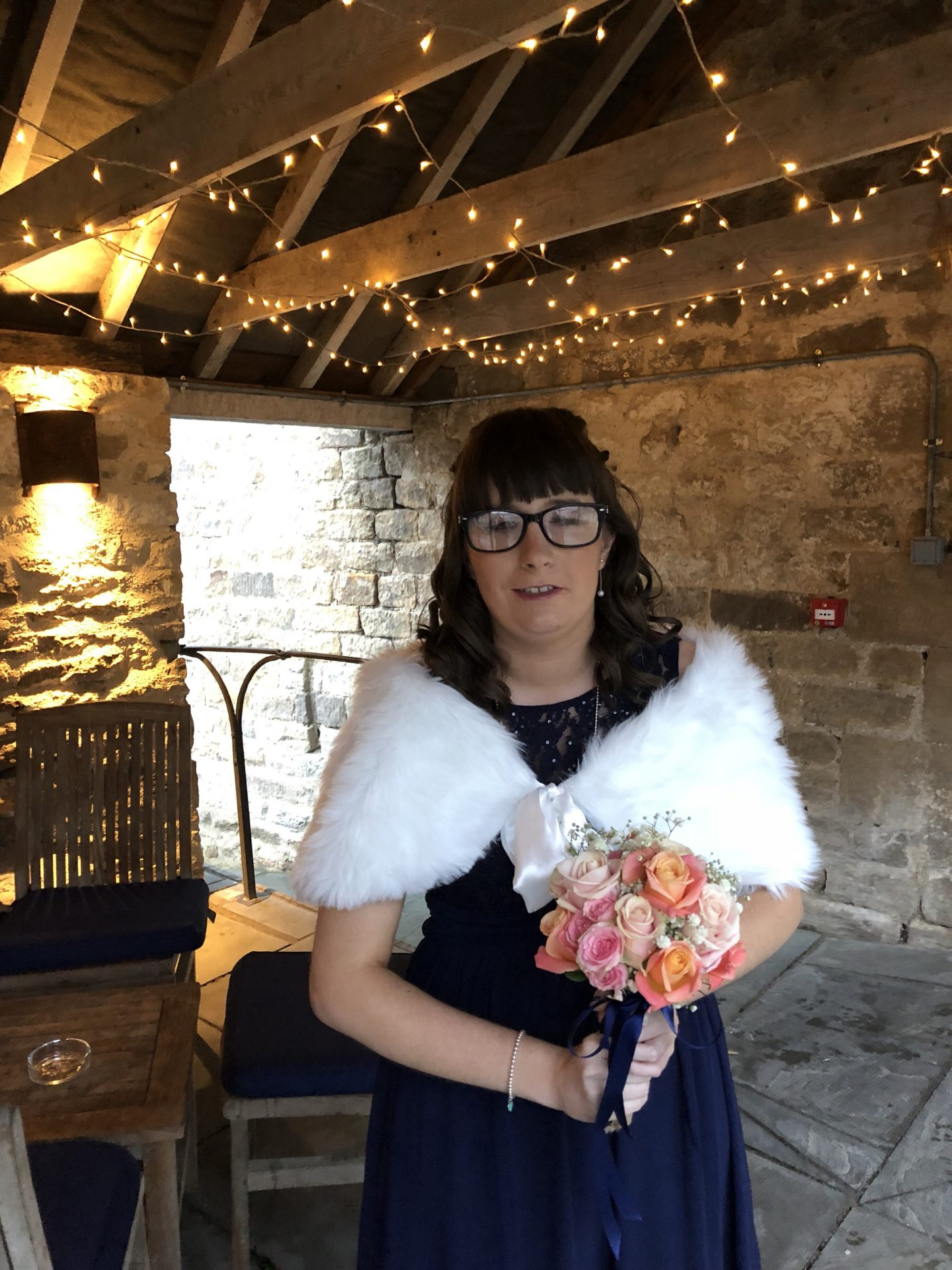 Holly wearing a blue bridesmaid dress, fur shrug and holding a bouquet