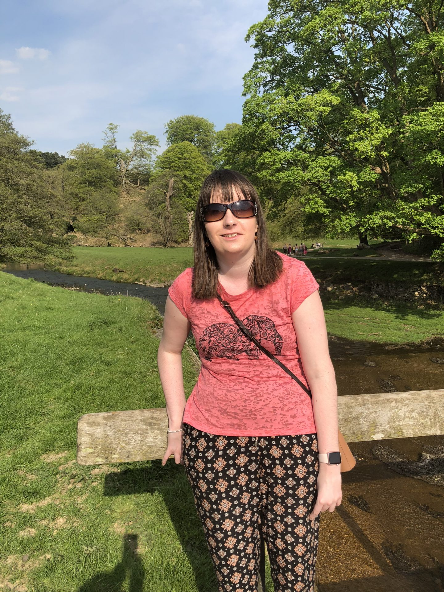 Holly wearing sunglasses, top and trousers with a waterfall in the background