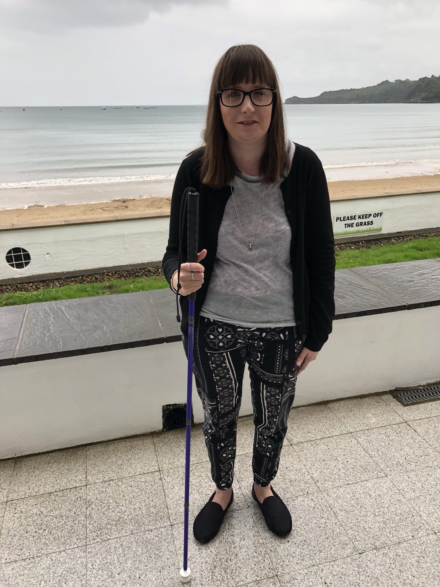 A photo of Holly holding a purple cane with the sea in the background