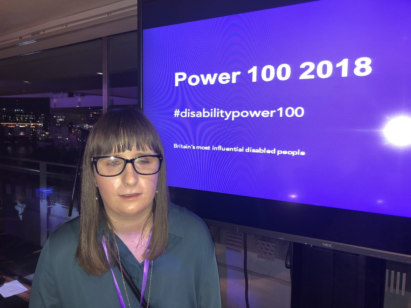 A photo of Holly with the 'Disability Power 100 2018' screen in the background
